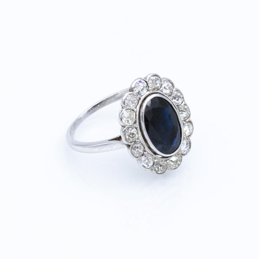 Bague entourage en or gris, pierre bleue et 14 diamants